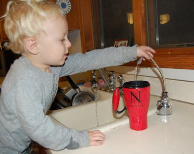 child at faucet