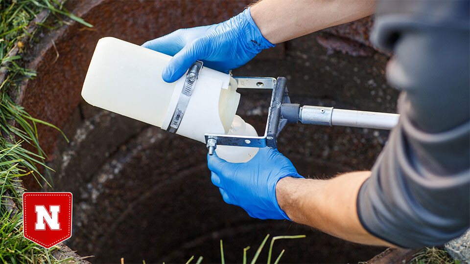 A graduate student collects a wastewater sample from a sewer connected to Harper Residence Hall.