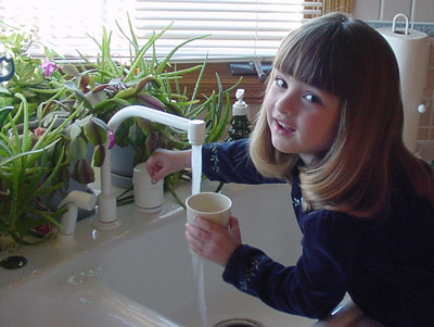 Girl getting a drink of water from the sink