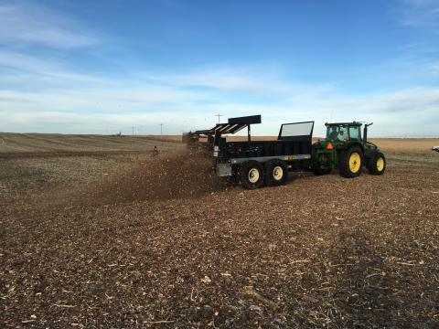 photo of spreading cedar mulch and manure with manure spreader and tractor