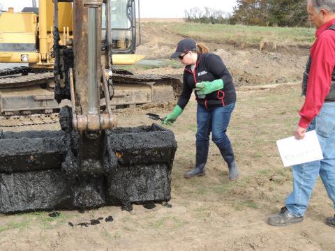 person sampling lagoon sludge from an excavator bucket