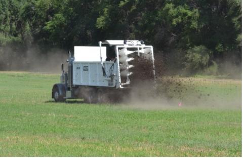 Typical manure spreader broadcasting manure solid to soil as fertilizer amendment.